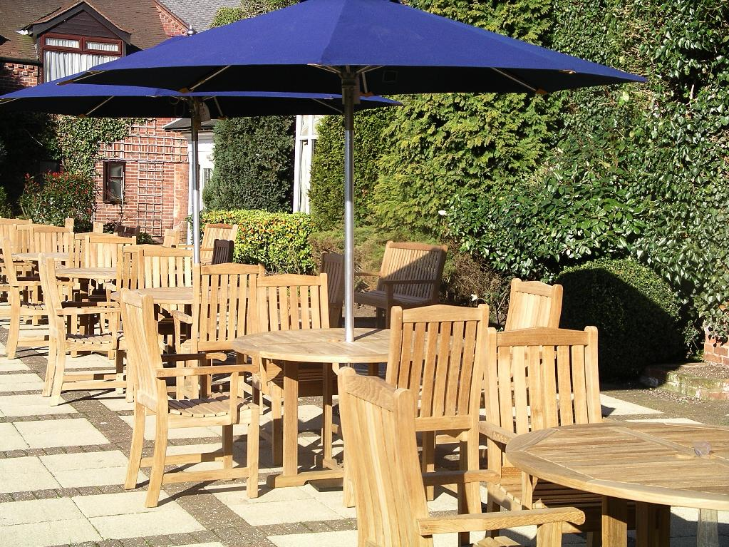 Teak round table and chairs shining a rich golden brown in the afternoon sun at The Belfry.